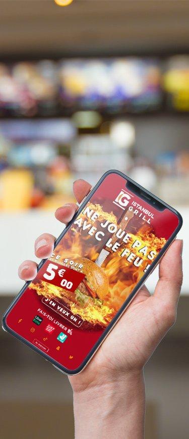 Smartphone tenu en main montrant une promotion pour un restaurant rapide